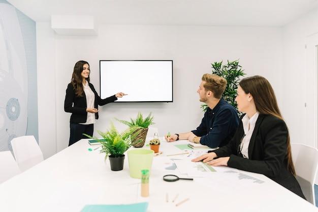 Feliz empresaria dando presentación a sus socios en reunión de negocios