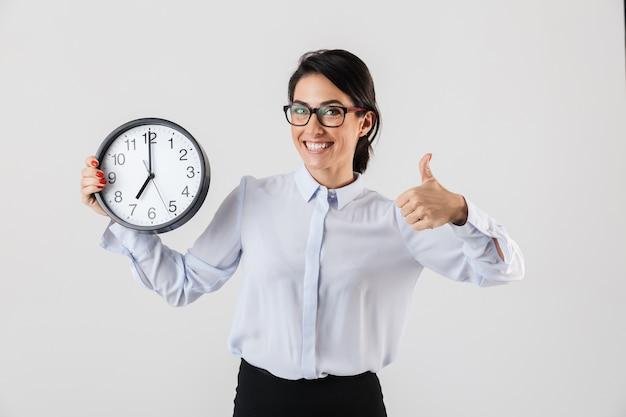 Feliz empresaria emocionada elegantemente vestida que se encuentran aisladas sobre una pared blanca, mostrando el despertador