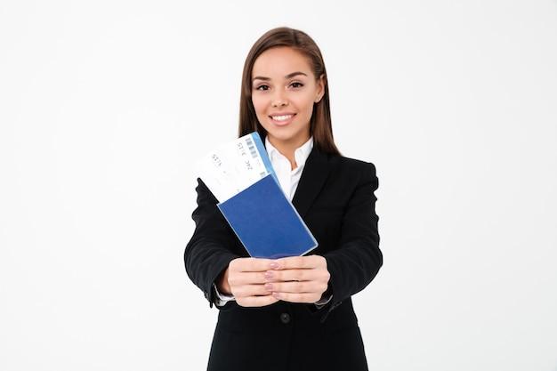 Feliz empresaria linda mostrando boletos y pasaporte
