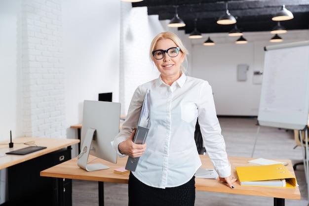 Feliz empresaria de pie y sosteniendo carpetas apoyado en el escritorio en la oficina