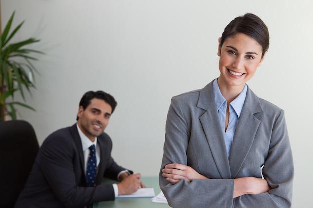 Feliz empresaria posando mientras su colega está trabajando