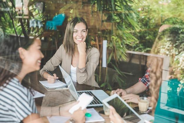 Feliz empresaria sonriendo mientras se reúne con su equipo en la cafetería.