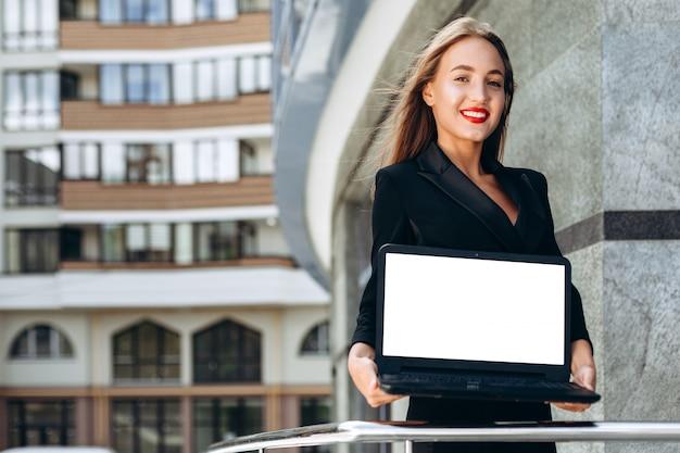 Feliz empresaria sosteniendo una maqueta en blanco pantalla blanca del portátil.- imagen horizontal