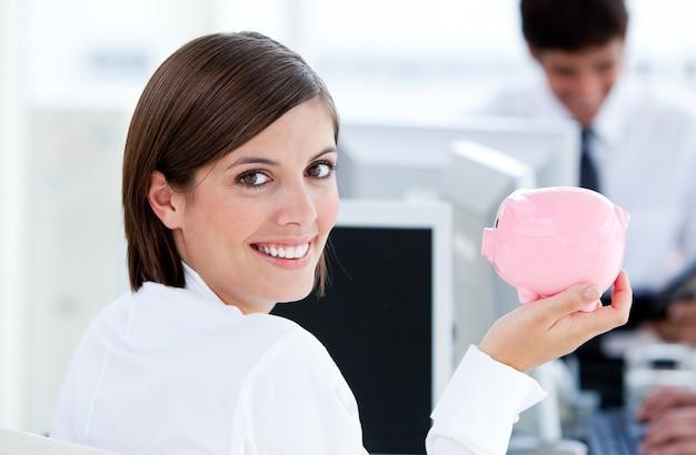 Feliz empresaria sosteniendo un piggybank