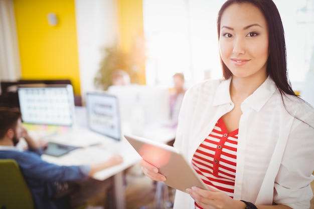 Feliz empresaria con tablet pc en la oficina creativa