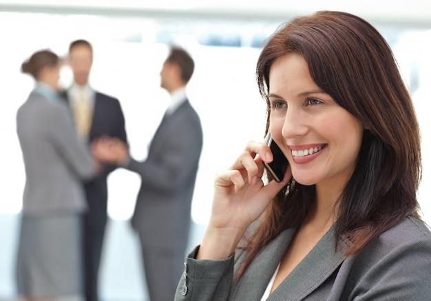 Feliz empresaria en el teléfono mientras su equipo está trabajando
