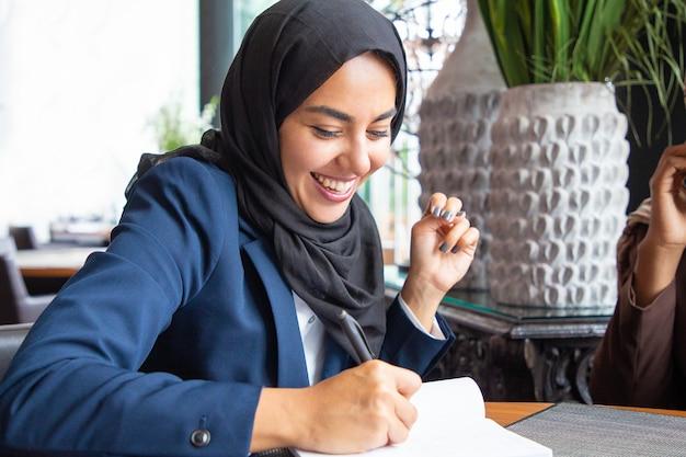 Feliz empresaria tomando notas