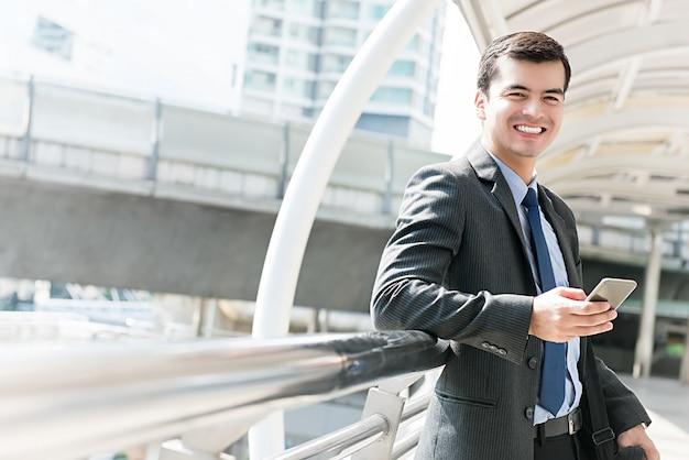 Feliz empresario hispano sonriente usando teléfono móvil al aire libre en la ciudad