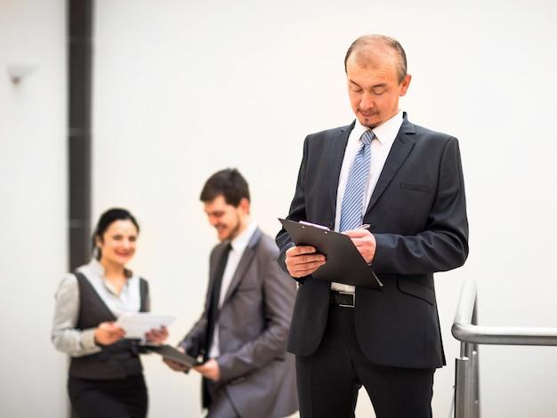 Feliz empresario maduro mirando a la cámara con satisfacción en la oficina