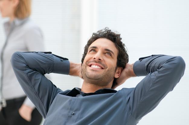 Feliz empresario sonriente mirando hacia arriba con expresión soñando en la oficina