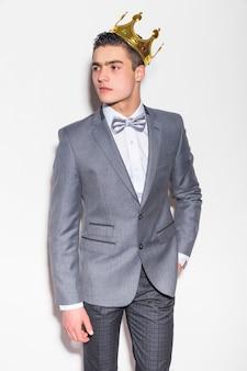 Feliz empresario sonriente en traje gris y corona, aislado sobre pared blanca