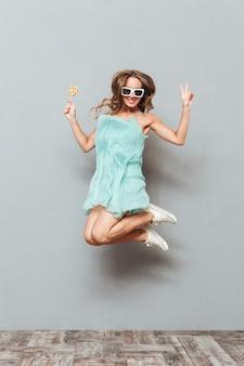 Feliz encantadora joven en gafas de sol saltando en el aire