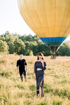 Feliz encantadora joven en ropa negra de moda, de pie en el hermoso campo verde de verano, mientras su novio camina hacia ella