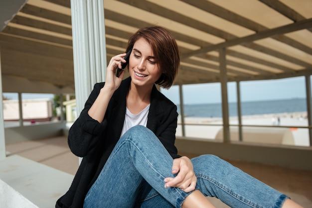 Feliz encantadora joven sentada y hablando por teléfono celular en la glorieta en la playa