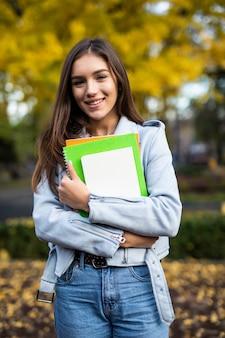 Feliz encantadora mujer joven con mochila de pie y sosteniendo portátiles en el parque
