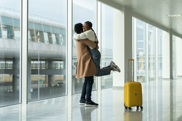 Feliz encuentro en el aeropuerto, el hombre africano se reunió y abrazó a la mujer después de su llegada a la moderna terminal vacía