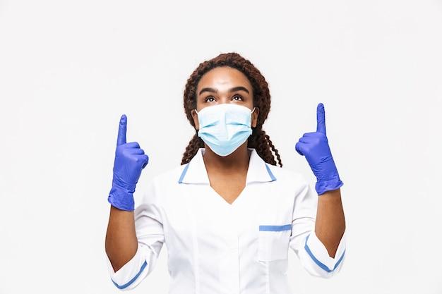 Feliz enfermera con mascarilla médica y guantes desechables apuntando con el dedo al copyspace aislado contra la pared blanca