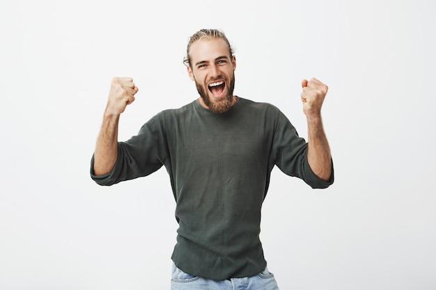 Feliz y entusiasta padre barbudo con ropa elegante gritando