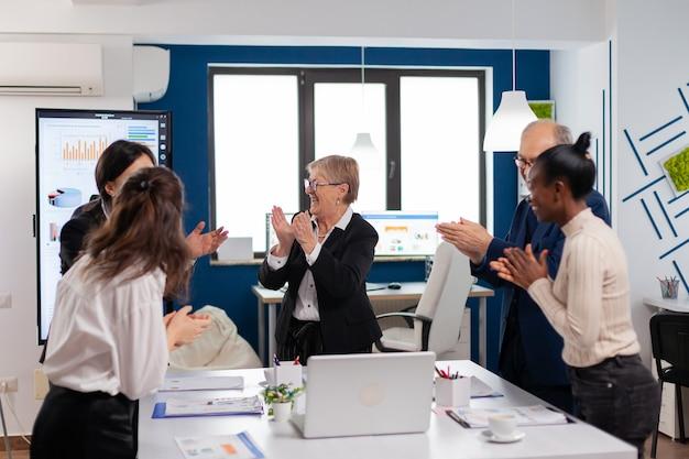 Feliz equipo diverso emocionado del equipo financiero en la sala de conferencias después de una estrategia exitosa