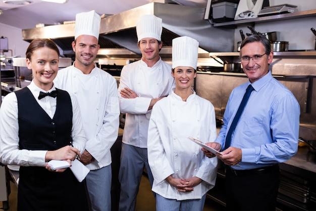 Feliz equipo de restaurante de pie juntos en la cocina comercial