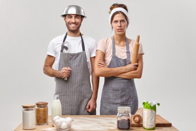Feliz esposo en delantal sostiene un batidor, la esposa enojada mantiene las manos cruzadas, se para cerca de la mesa de la cocina, preparan la cena juntos, rodeados de todos los ingredientes necesarios, aislados en la pared blanca