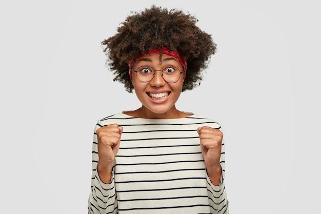 Feliz estudiante africano se siente como un ganador, aprieta los puños en señal de triunfo, feliz de aprobar todos los exámenes con éxito