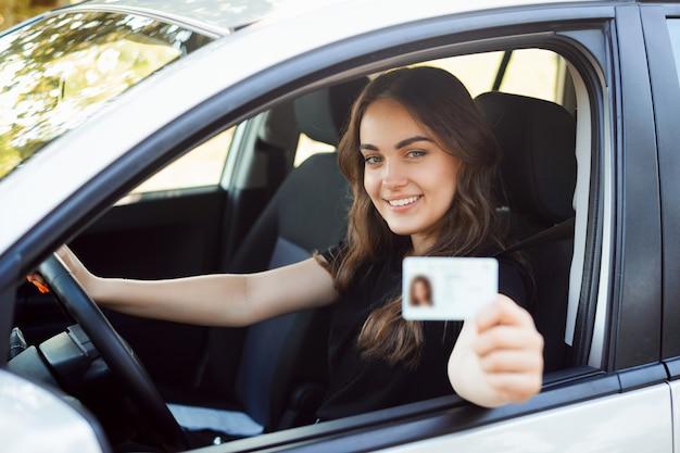 Feliz estudiante conductor sentado en el moderno coche plateado y mostrando el permiso de conducir