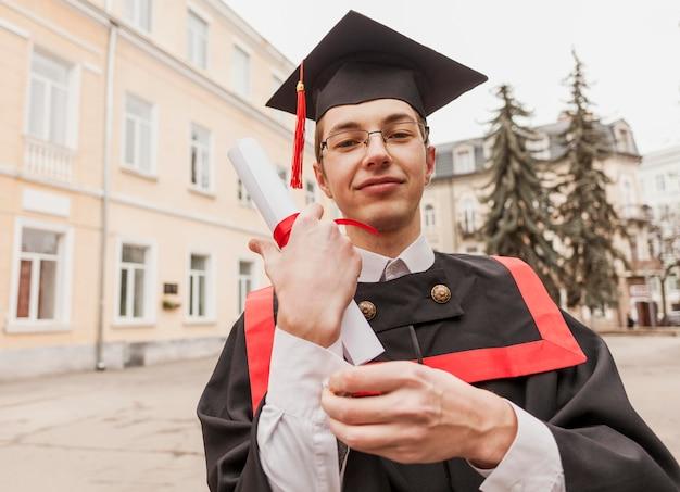 Feliz estudiante graduado con diploma