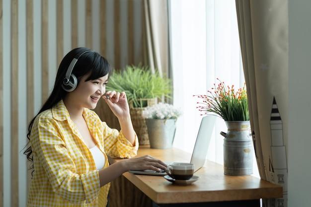 Feliz estudiante mujer asiática usa audífonos estudiando el curso en línea y se comunica por videollamada de conferencia, usando una computadora portátil