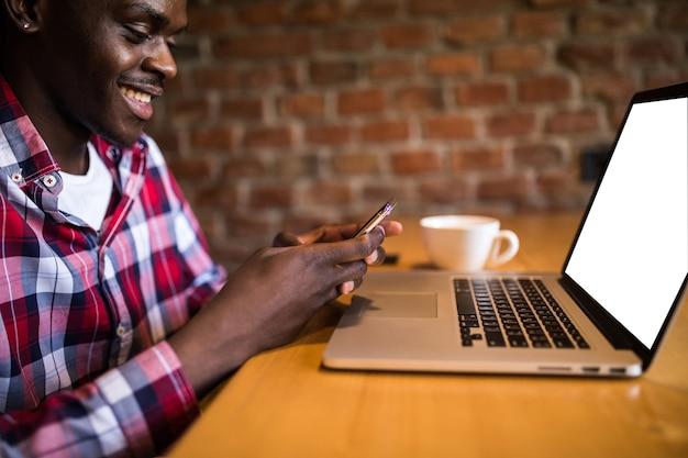 Feliz estudiante universitario afroamericano con linda sonrisa escribiendo un mensaje de texto en un dispositivo electrónico, sentado en el café tablein cafe.