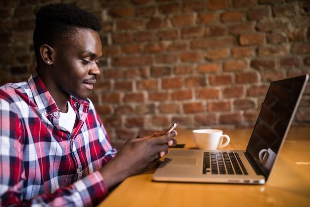 Feliz estudiante universitario afroamericano con linda sonrisa escribiendo mensajes de texto en el teléfono, sentado en el café