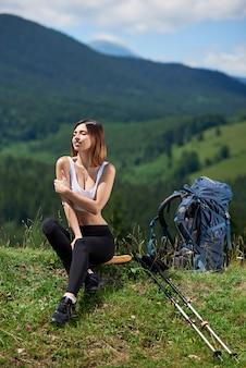Feliz excursionista femenina con mochila y bastones de trekking disfrutando día soleado en una hierba con los ojos cerrados, en las montañas. concepto de estilo de vida activo
