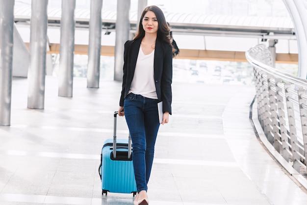Feliz exitosa empresaria caminando con equipaje