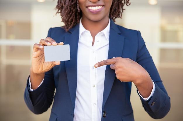Feliz exitosa mujer de negocios que muestra la tarjeta de identificación