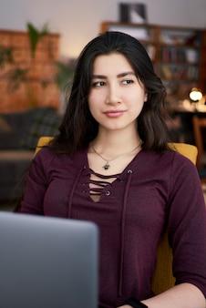 Feliz exitosa mujer de negocios trabajando en la computadora portátil en el lugar de trabajo conjunto, sonriente mujer empresaria usando la computadora portátil en la cafetería