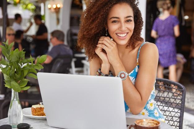 Feliz exitoso y talentoso joven redactora afroamericana trabaja en una computadora portátil en el restaurante