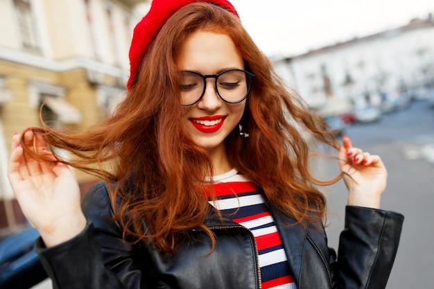 Feliz fabulosa mujer de jengibre en elegante boina roja en la calle