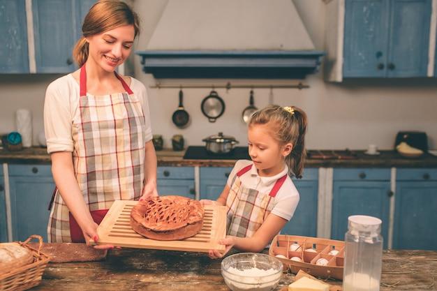 Feliz familia amorosa están preparando panadería juntos. madre e hija niña divirtiéndose en la cocina. orgullosamente sosteniendo pastel casero recién horneado.
