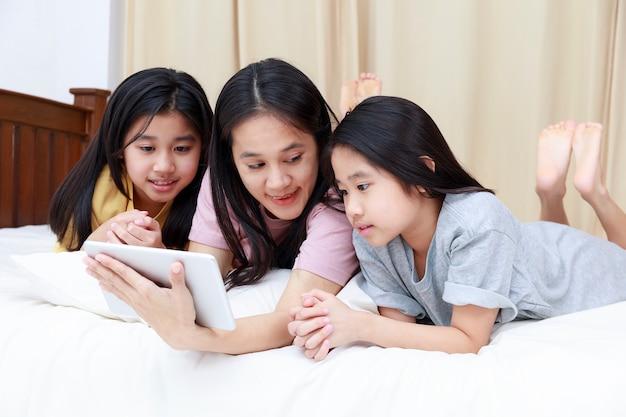 Feliz familia asiática disfrutar y relajarse en la cama en el dormitorio madre e hijas disfrutan de usar la tableta juntos
