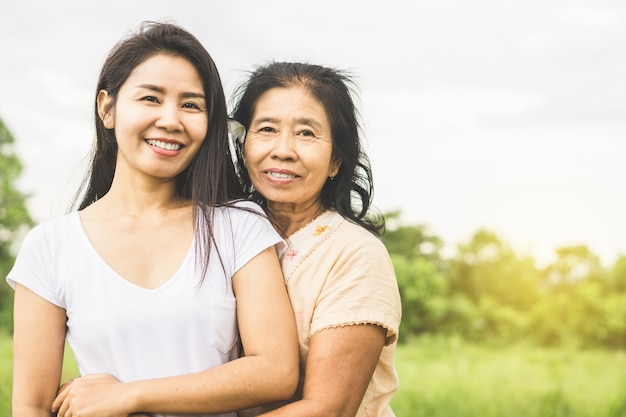 Feliz familia asiática madre e hija abrazándose en un parque