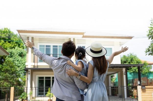 Feliz familia asiática. padre, madre e hija cerca de casa nueva. bienes raíces