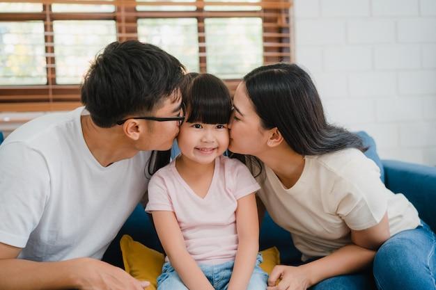 Feliz familia asiática papá, mamá e hija abrazándose besándose en la mejilla felicitando con cumpleaños en casa.