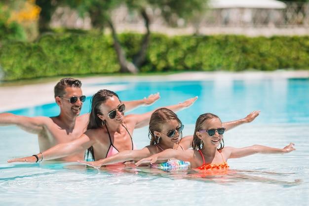 Feliz familia de cuatro en piscina al aire libre