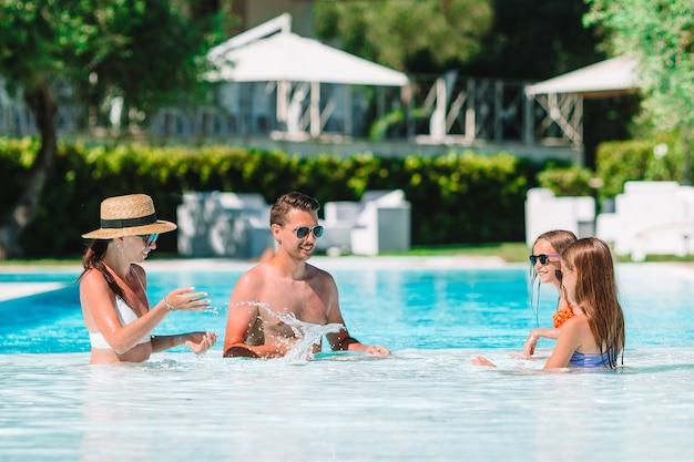 Feliz familia de cuatro en la piscina al aire libre