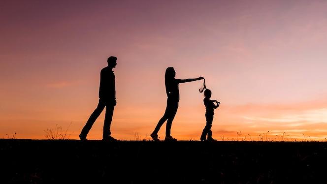 Feliz familia de cuatro personas, madre, padre e hija en el prado.