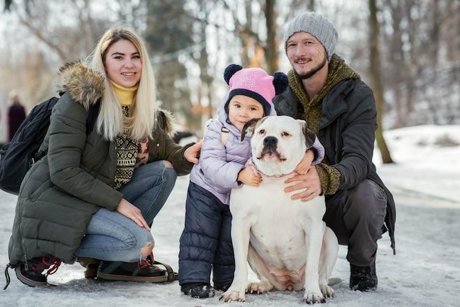 Feliz familia de mamá, papá y pequeña hija posan con bulldogs estadounidenses en el parque