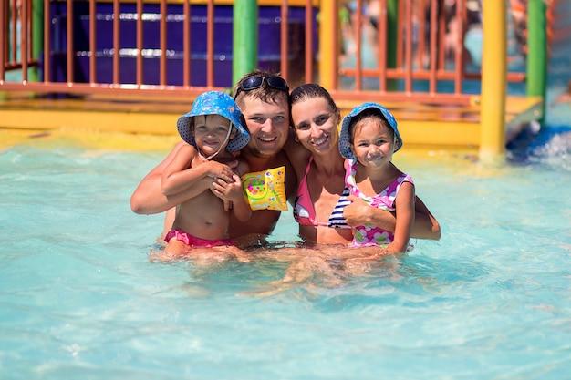 Feliz familia europea con dos hijos nadando en la piscina de un gran parque acuático hermoso durante las vacaciones de verano