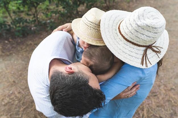 Feliz familia hispana abrazándose el uno al otro al aire libre