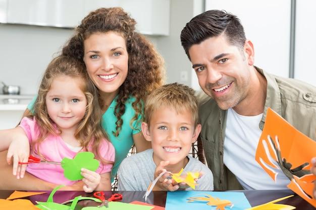 Feliz familia joven haciendo manualidades en la mesa