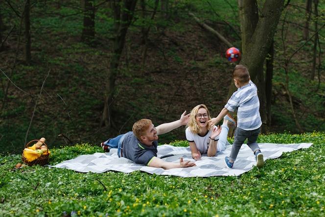 Feliz familia joven juega con una pelota sobre la tela escocesa durante un picnic en el parque